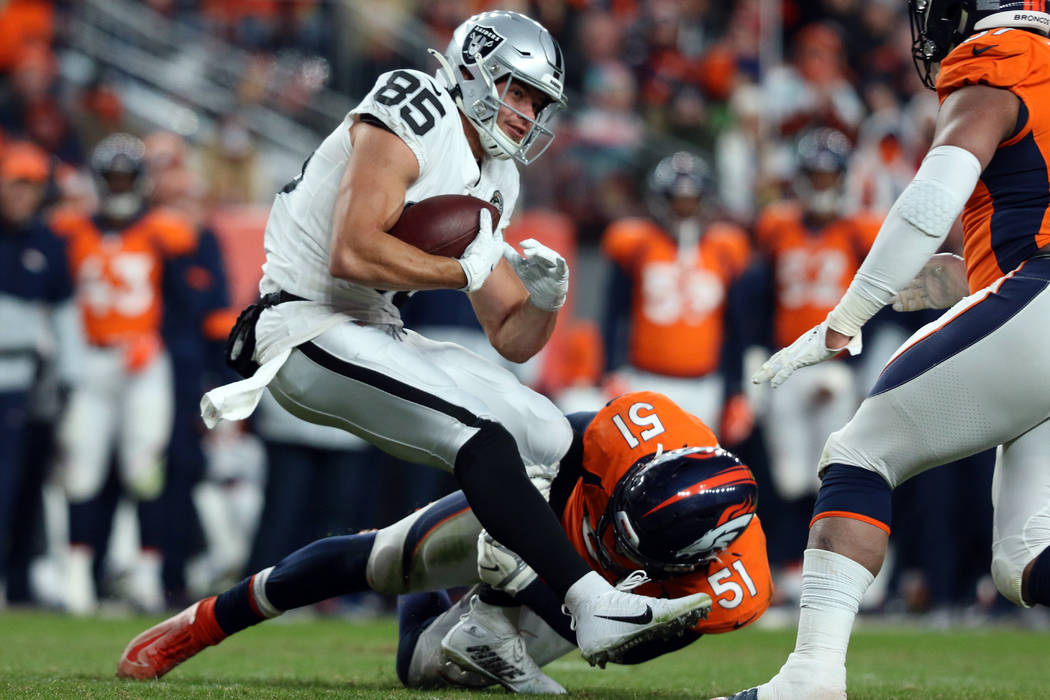 Oakland Raiders tight end Derek Carrier (85) is tackled by Denver Broncos inside linebacker Tod ...