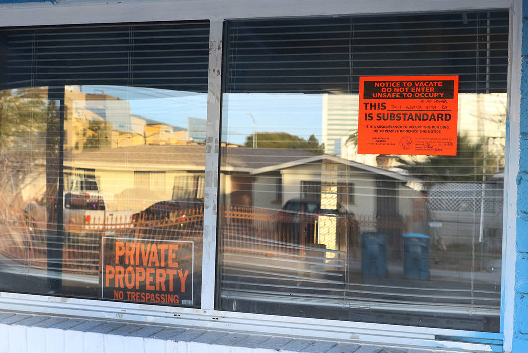 """""""Private Property"""" and """"Unsafe to Occupy"""" signs are posted on the window of a house at 2017 S. ..."""