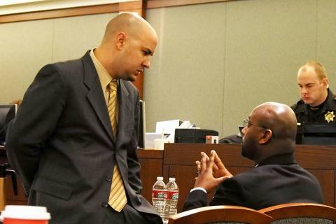 Attorney Jack Buchanan, left, talks with his client Benjamin Hawkins, right, during a recess at ...