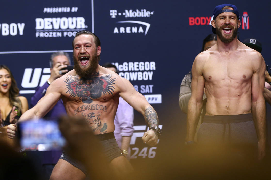 """Conor McGregor, left, and Donald """"Cowboy"""" Cerrone poses for photos ahead of their wel ..."""