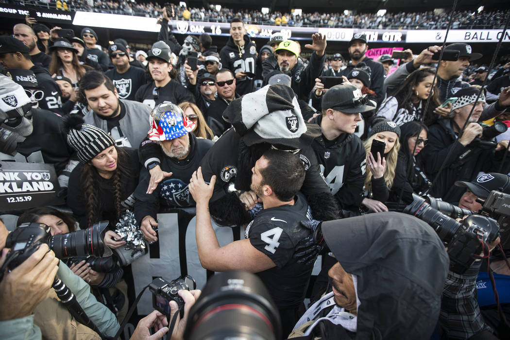 "Oakland Raiders quarterback Derek Carr (4) hugs fans in the ""Black Hole"" after Oakland lost to ..."
