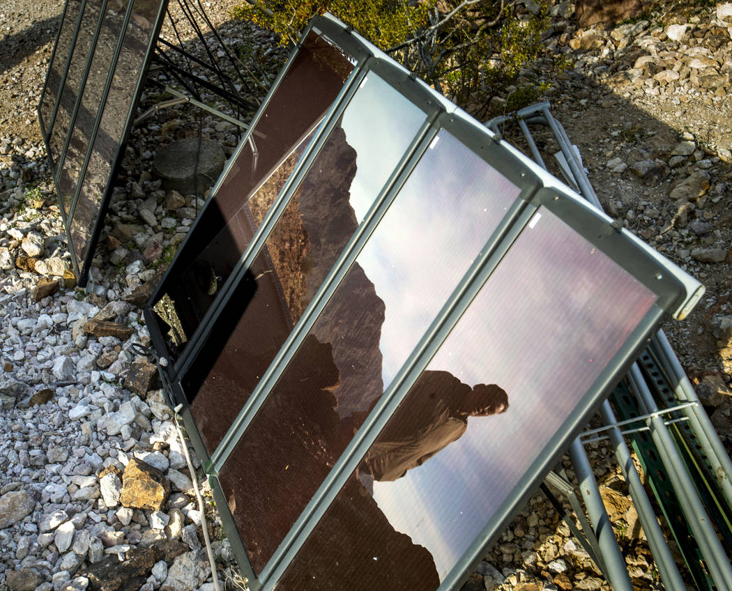 Richard Roman is reflected in one of his solar panels as he continues to clean out his cave aft ...