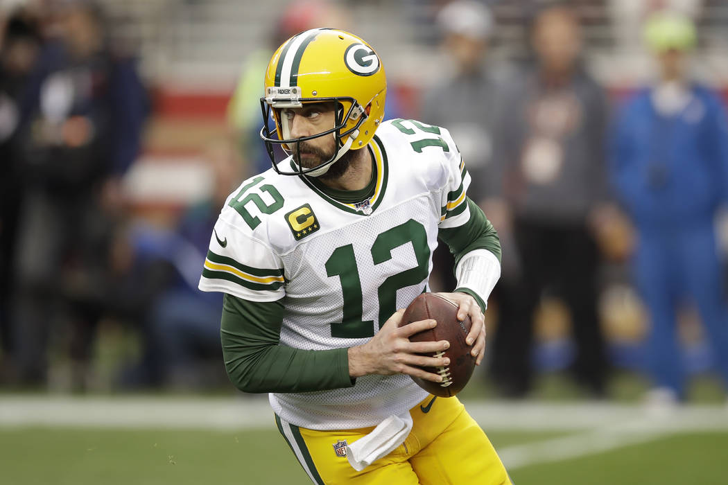 Green Bay Packers quarterback Aaron Rodgers (12) rolls out during the first half of the NFL NFC ...