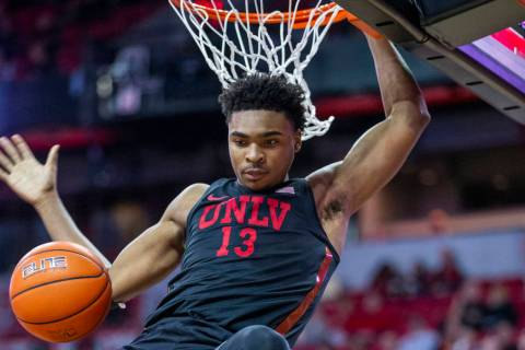 UNLV Rebels guard Bryce Hamilton (13,) drives on dunks the ball over New Mexico Lobos forward C ...