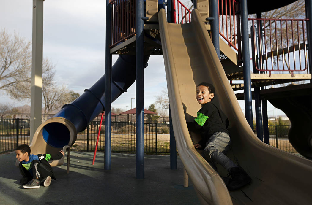 Twins Manny Drexler and Sammy Drexler, 5, play on the slides at Justice Myron E. Leavitt & ...