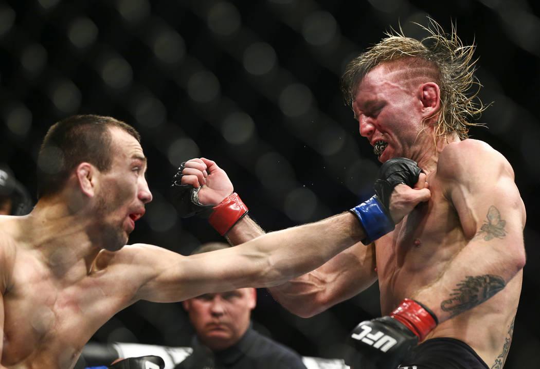 Tim Elliott, right, takes a hit from Askar Askarov during their flyweight bout at UFC 246 at T- ...