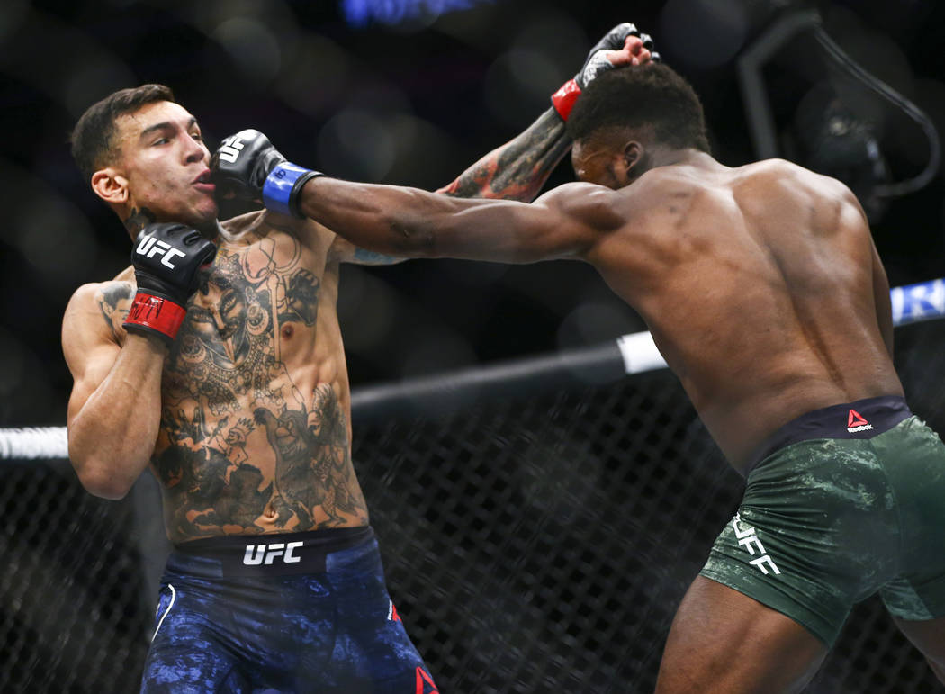 Andre Fili, left, takes a hit from Sodiq Yusuff during their featherweight bout at UFC 246 at T ...