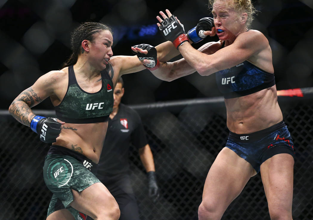 Holly Holm, right, takes a hit from Raquel Pennington during their bantamweight bout at UFC 246 ...