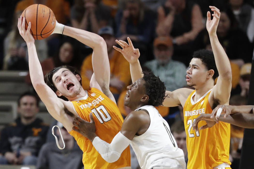 Tennessee forward John Fulkerson (10) loses his headband as he grabs a rebound in front of Vand ...