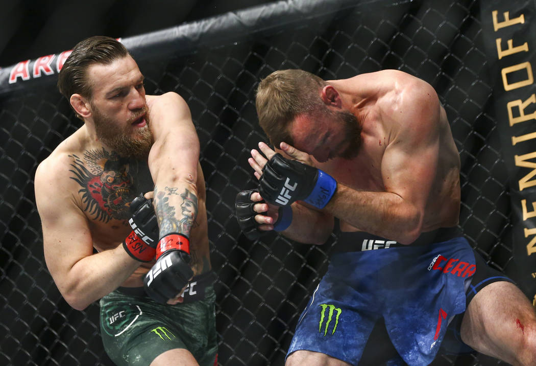 """Conor McGregor, left, fights Donald """"Cowboy"""" Cerrone during their welterweight bout a ..."""