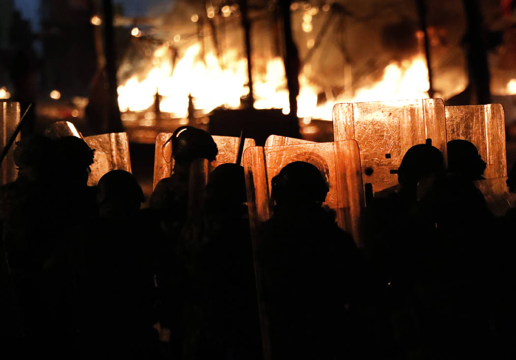Riot policemen watch flames rise from the tents of anti-government protesters, which where set ...