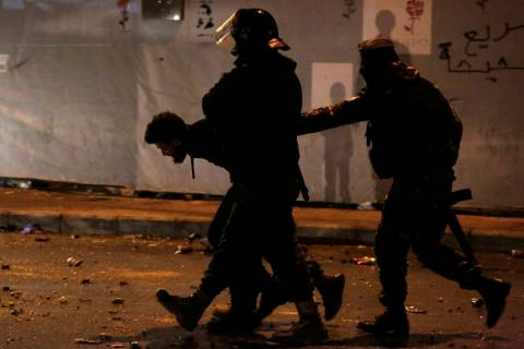 Lebanese police arrest an anti-government protester after dispersing a protest in Beirut, Leban ...