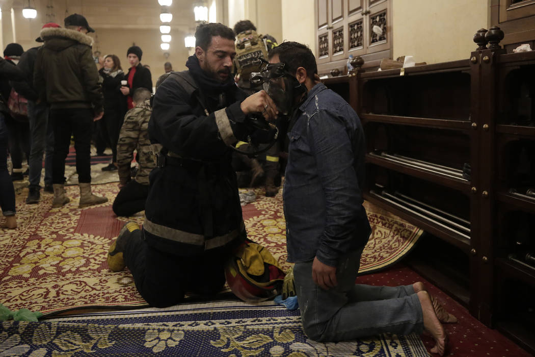 An anti-government protester receives treatment after confrontation with Lebanese riot police i ...