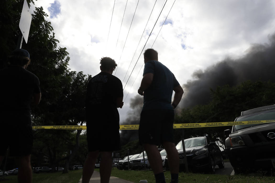 Bystanders watch black smoke billowing from a house fire after a shooting and domestic incident ...