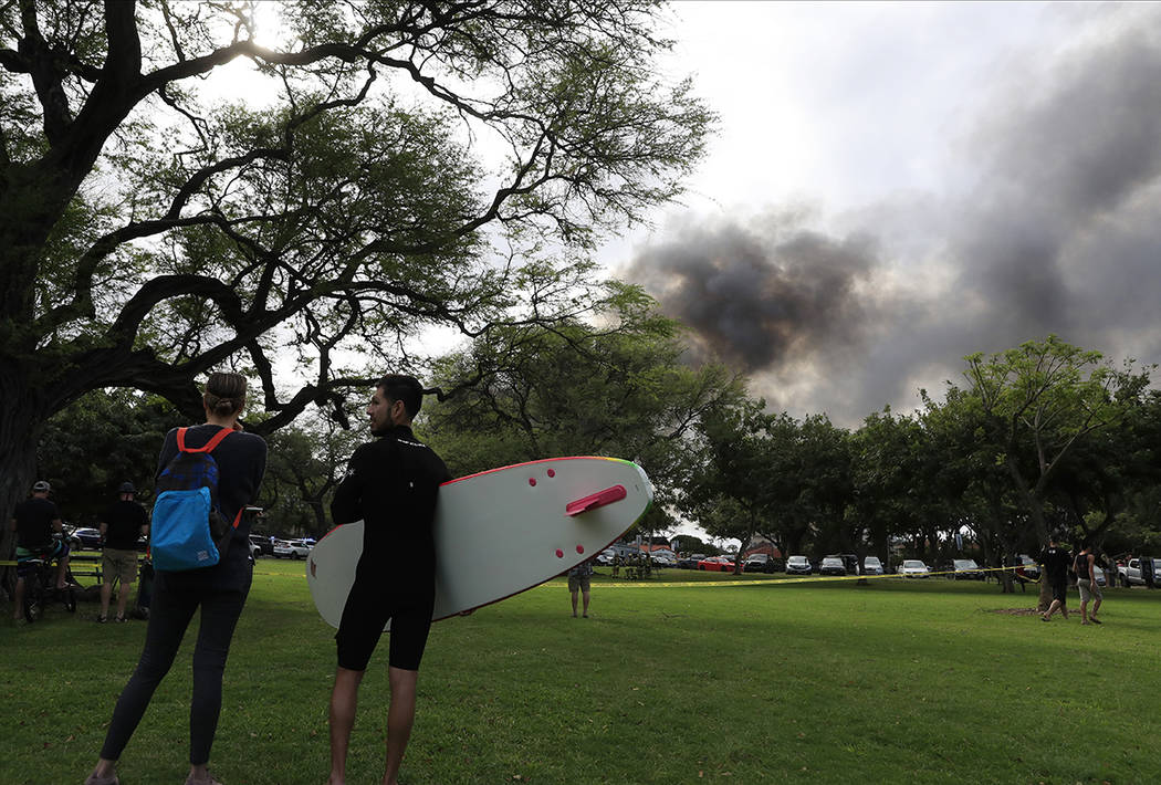 Aina Haina resident Kai Ohashi, right, and Waikiki resident Lucy Taylor observe billowing smoke ...