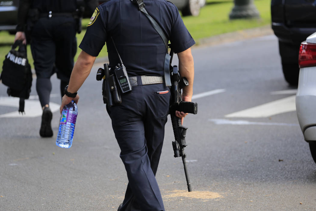 A Honolulu police officer carries an assault rifle near the scene of multiple house fires in a ...