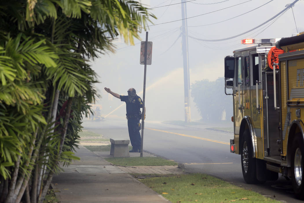 A Honolulu police officer directs traffic near the scene of multiple house fires in the Diamond ...