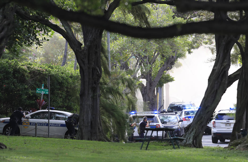 Honolulu police take up defensive positions with their weapons after a shooting and domestic in ...