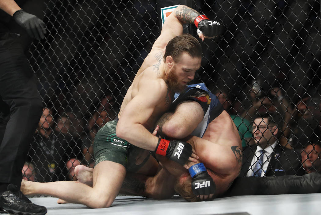 "Conor McGregor, left, fights Donald ""Cowboy"" Cerrone during a UFC 246 welterweight mi ..."