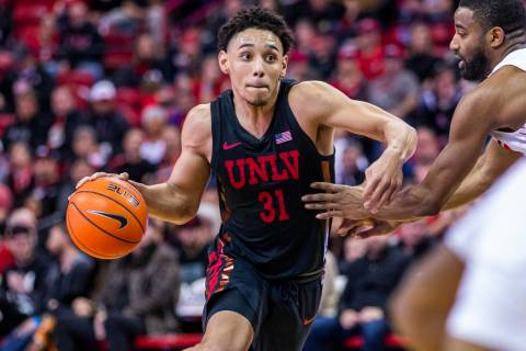 UNLV Rebels guard Marvin Coleman (31, center) drives the lane versus New Mexico Lobos guard JaQ ...