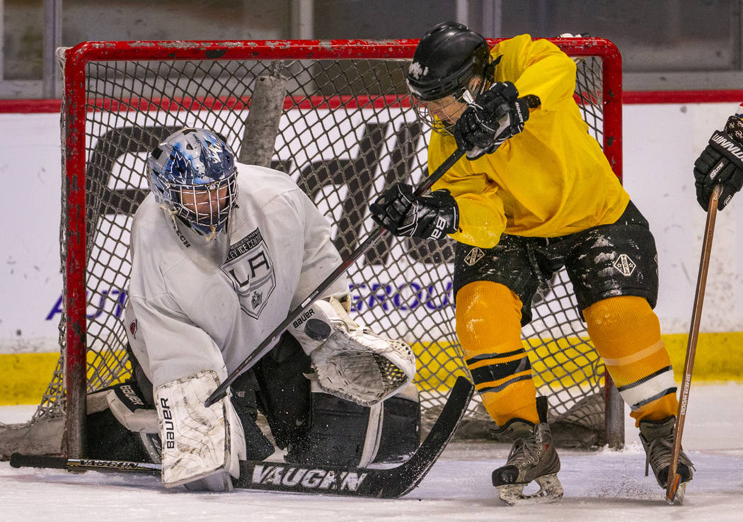 Team Redrum goalie John Hunt, left, deflects the puck while facing the Golden Knights in their ...