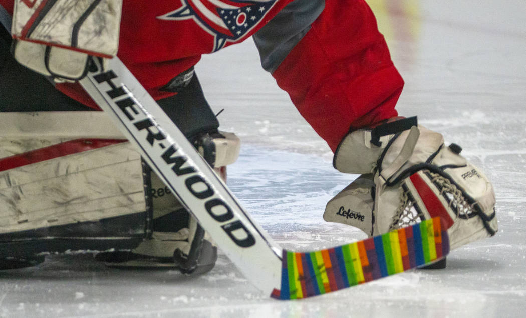 Flamingos goalie makes a stop sporting a rainbow-wrapped stick against the Blackjacks during th ...
