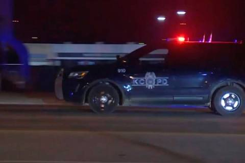 In this image made from video, a police vehicle passes with sirens near the scene of a shooting ...