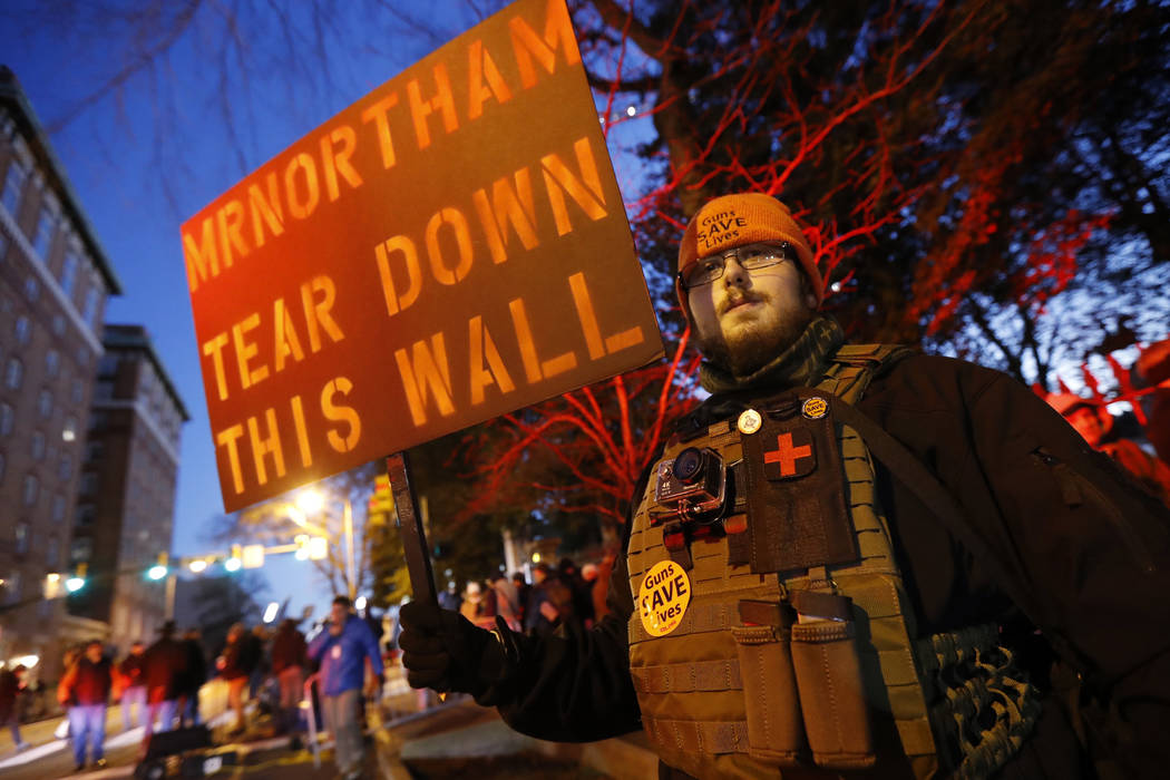 A demonstrator stands on the sidewalk before a pro gun rally, Monday, Jan. 20, 2020, in Richmon ...