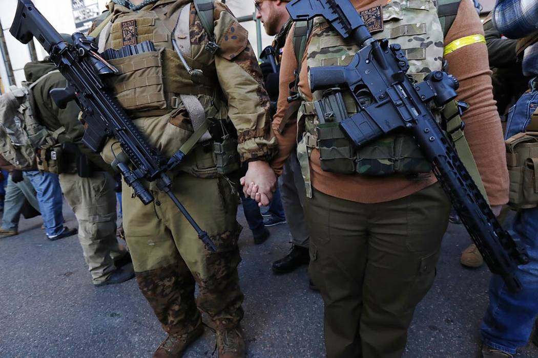 Demonstrators stand outside a security zone before a pro gun rally, Monday, Jan. 20, 2020, in R ...