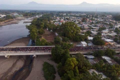 Migrants gather at the bridge spanning the Suchiate River in Tecun Uman, Guatemala, Monday, Jan ...