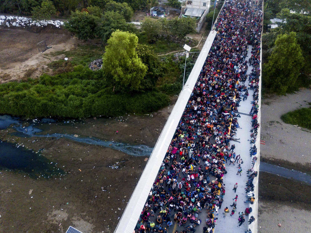 Migrants gather at the bridge spanning the Suchiate River in Tecun Uman, Guatemala, Monday, Jan ...
