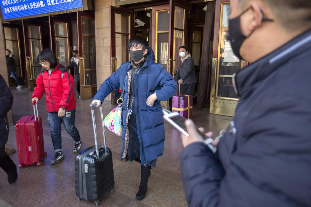 Travelers wear face masks as they walk outside of the Beijing Railway Station in Beijing, Monda ...
