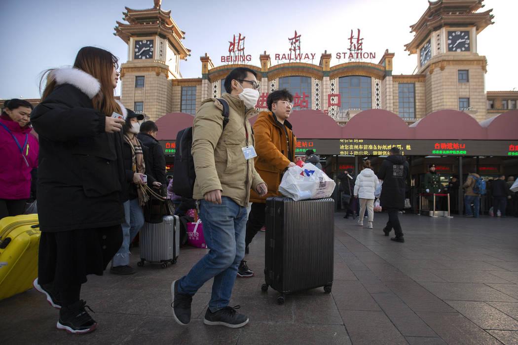 A traveler wears a face mask as he walks outside of the Beijing Railway Station in Beijing, Mon ...