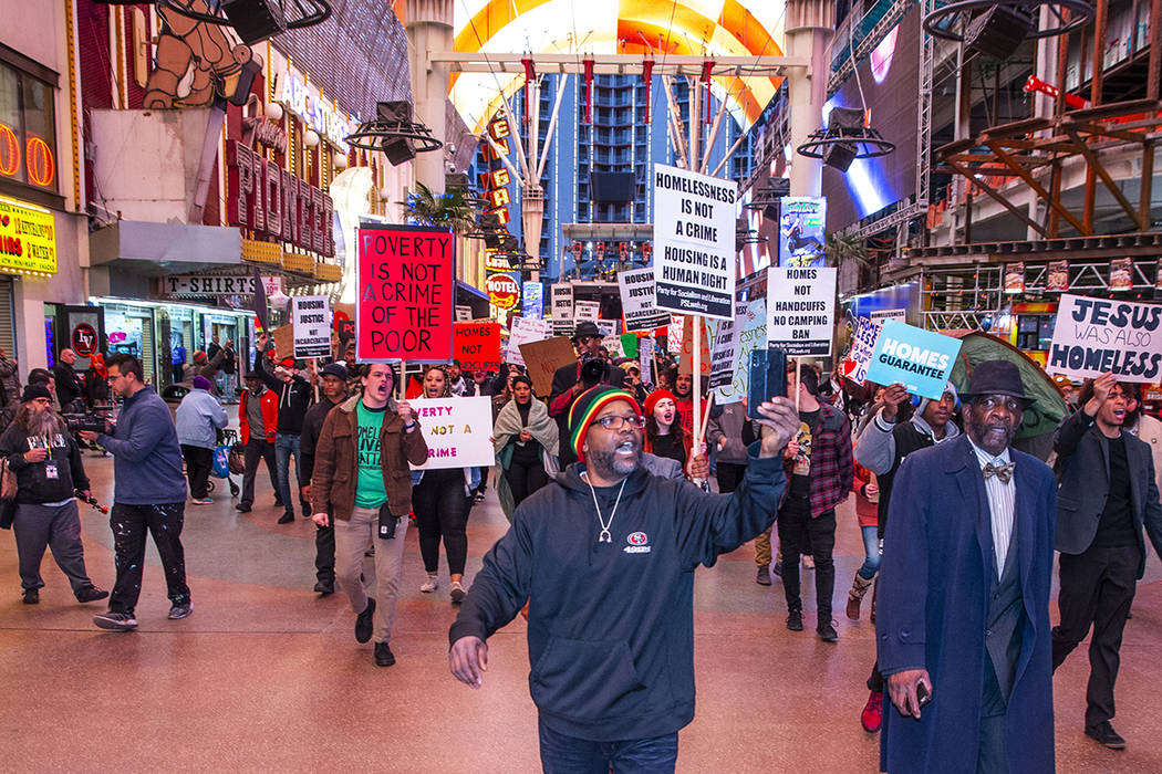 Local activists march through the Fremont Experience following a rally at the Las Vegas City Ha ...