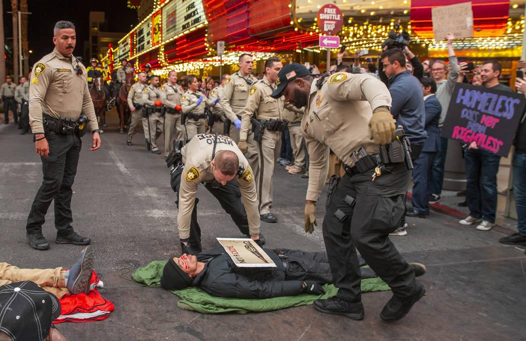 Las Vegas Metropolitan Police officers move in to arrest local activists blocking Casino Center ...