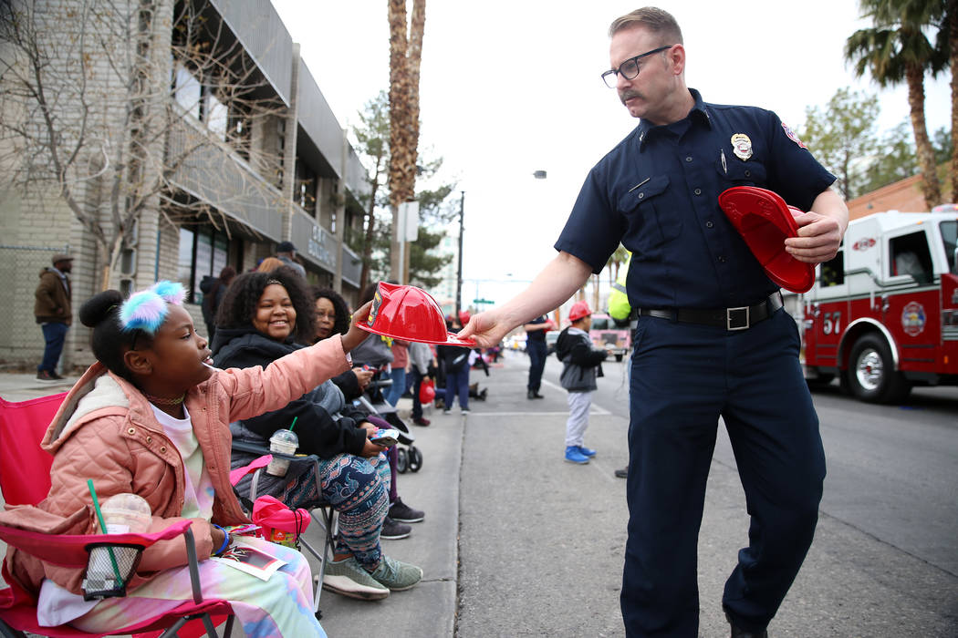 North Las Vegas Fire Department Captain Steve Wells, right, hands out a firefighter hat to Taja ...
