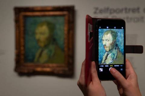 A journalist takes a picture of the previously contested painting by Dutch master Vincent van G ...