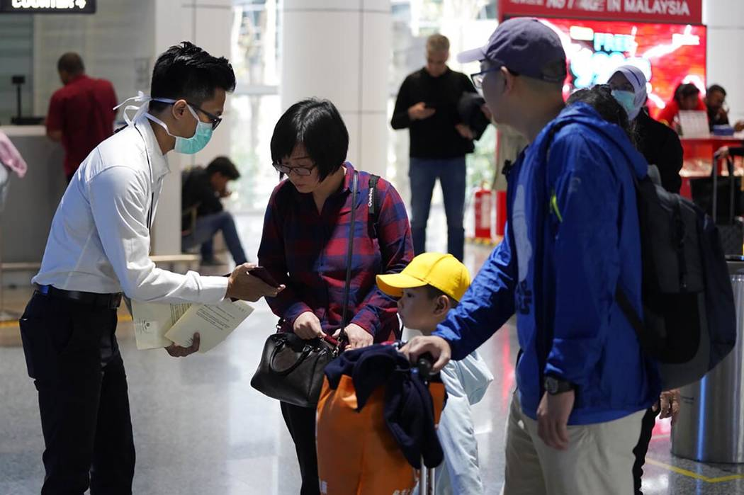 Health officials check passengers at the Kuala Lumpur International Airport in Sepang, Malaysia ...