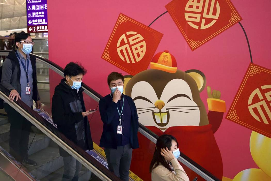 People wear face masks as they ride an escalator at the Hong Kong International Airport in Hong ...