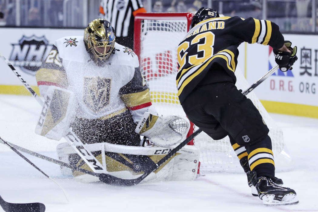 Vegas Golden Knights goaltender Marc-Andre Fleury, left, makes a save on a shot by Boston Bruin ...