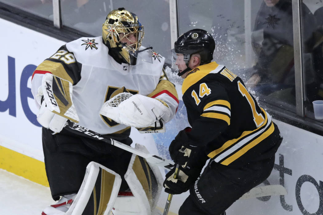 Boston Bruins right wing Chris Wagner (14) tangles with Vegas Golden Knights goaltender Marc-An ...