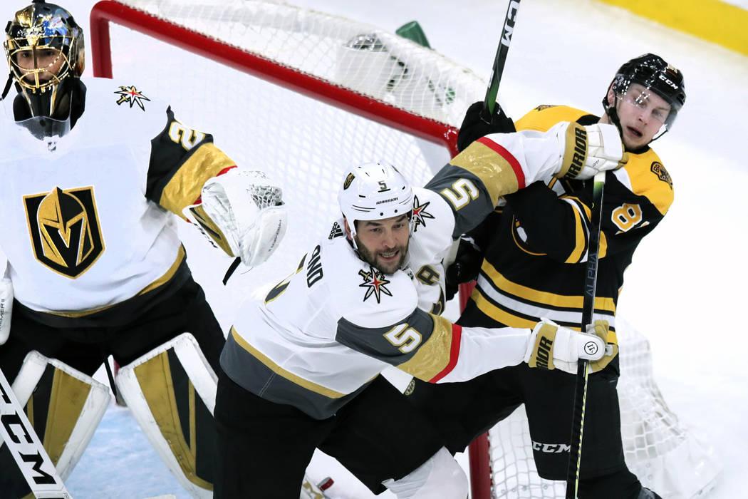 Vegas Golden Knights defenseman Deryk Engelland (5) tries to clear Boston Bruins Anton Blidh, r ...