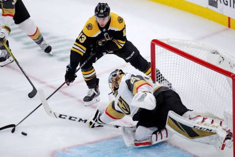 Vegas Golden Knights goaltender Marc-Andre Fleury, right, reaches for the puck against Boston B ...
