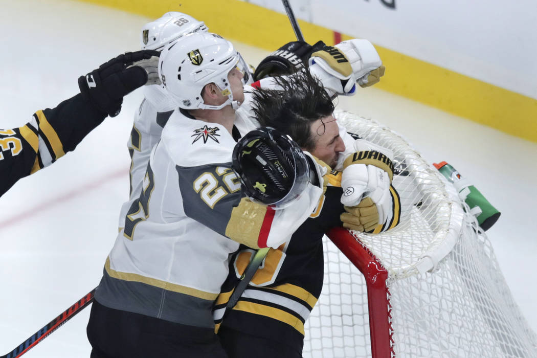 Boston Bruins left wing Brad Marchand is slammed into the goal by Vegas Golden Knights defensem ...