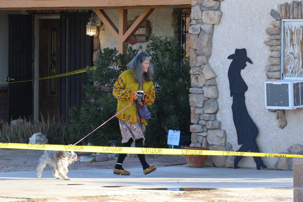 A woman and her dog leave the house where a person died in a shed fire at 2350 Lincoln Road on ...