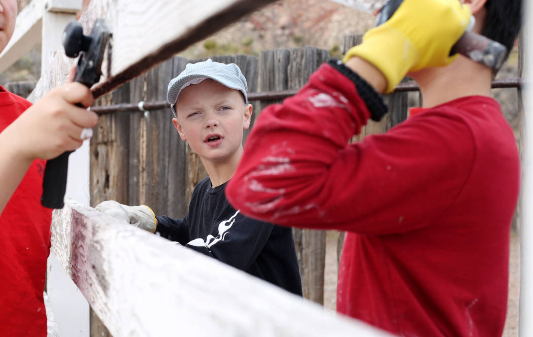 Micah Coombes, 11, with Scouts BSA of Las Vegas Troop 155, paints a fence during an outreach ou ...