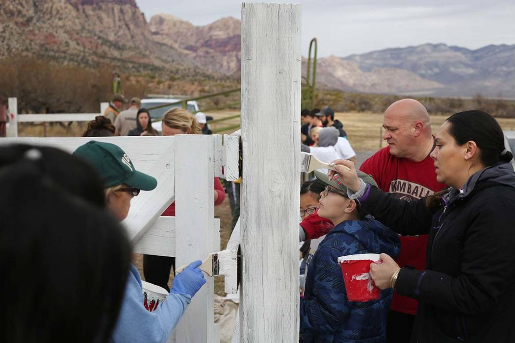 Volunteers with Scouts BSA paint a fence during their outreach day at Spring Mountain Ranch Sta ...