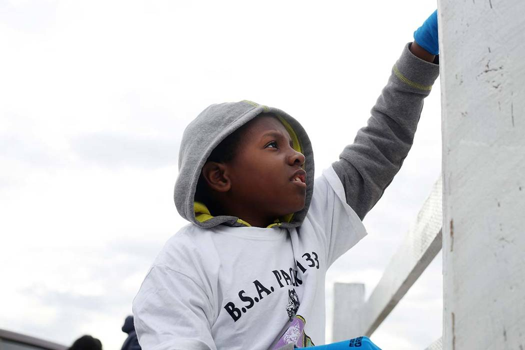 Jashon Cobbs, 11, with Scouts BSA of Las Vegas Troop 133, paints a fence during an outreach out ...