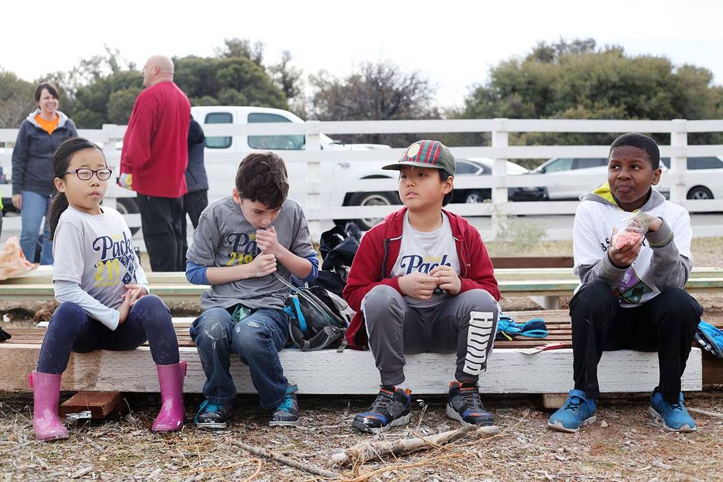 Volunteers with Scouts BSA take a break from painting a fence during their troop's outreach day ...