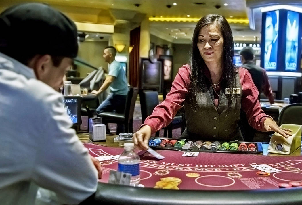 Table games dealer Dee Coffey, middle, deals blackjack at the MGM Grand hotel-casino on Thursda ...